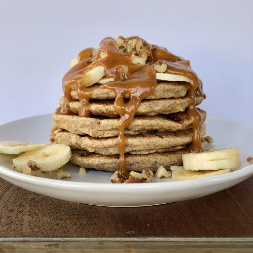 Stack of Vegan Banana Pancakes with Peanut Butter Syrup topped with sliced bananas and walnuts.