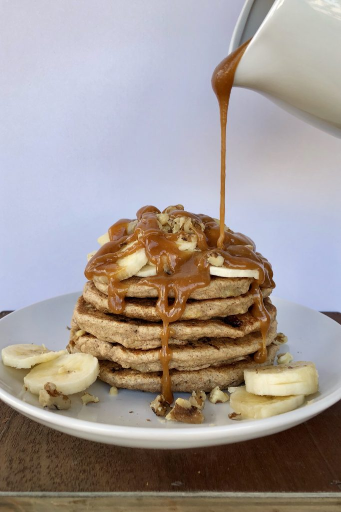 Stack of Vegan Banana Pancakes drizzled with Peanut Butter Syrup.