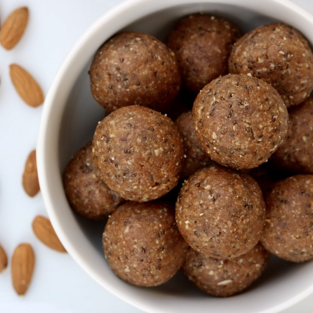 Bowl filled with Almond Energy Balls with almonds in the background.