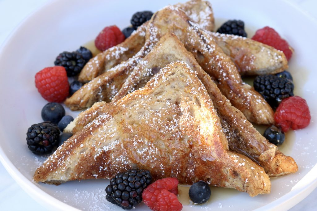 Close up, Healthy Vegan French Toast with fresh berries, syrup and powdered sugar.