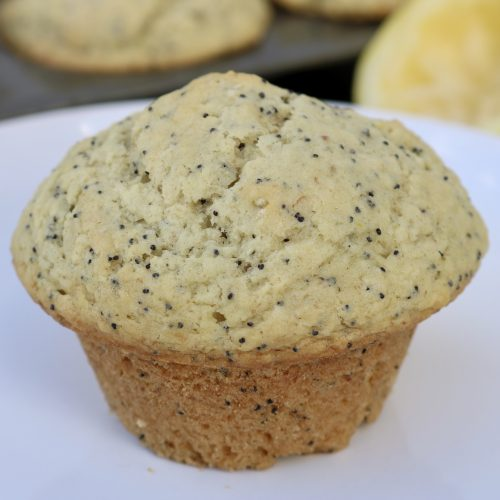 Close up, Vegan Lemon Poppy Seed Muffins with more muffins and a lemon in the background.