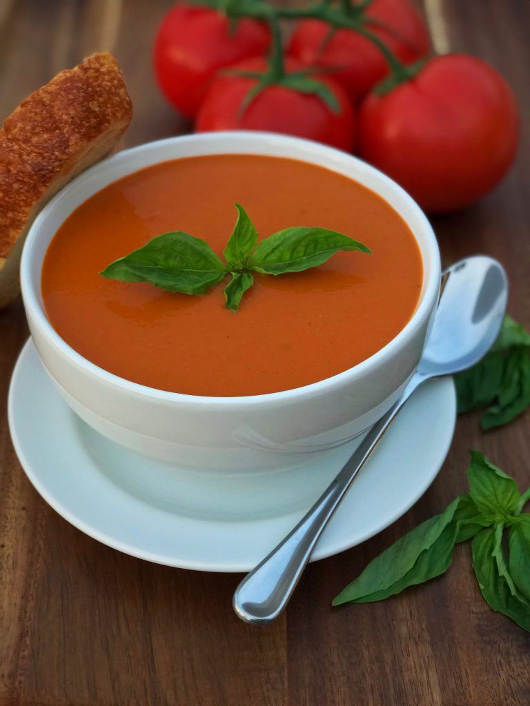 Bowl of Vegan Tomato Basil Soup with basil on top, a slice of baguette and tomato and basil in the background.