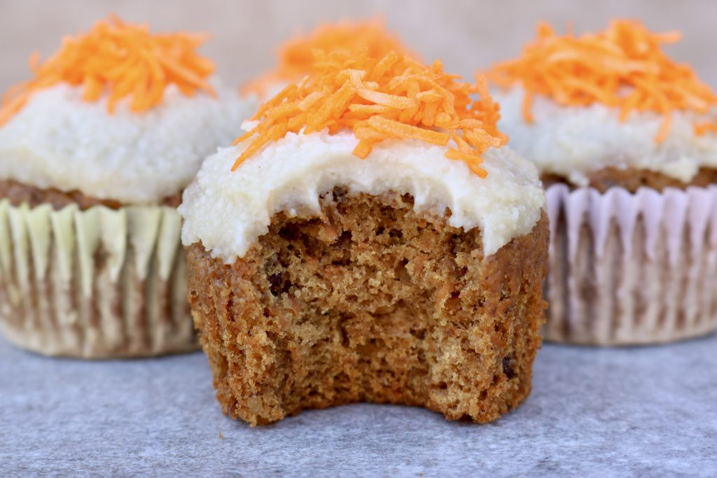 Close up, one Carrot Cake Cupcakes with Coconut Macadamia Nut Frosting with a bite out of it with two other cupcakes in the background.