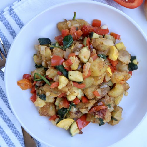Plate full of Vegetable Potato Hash with a napkin, fork and vegetables in the background.
