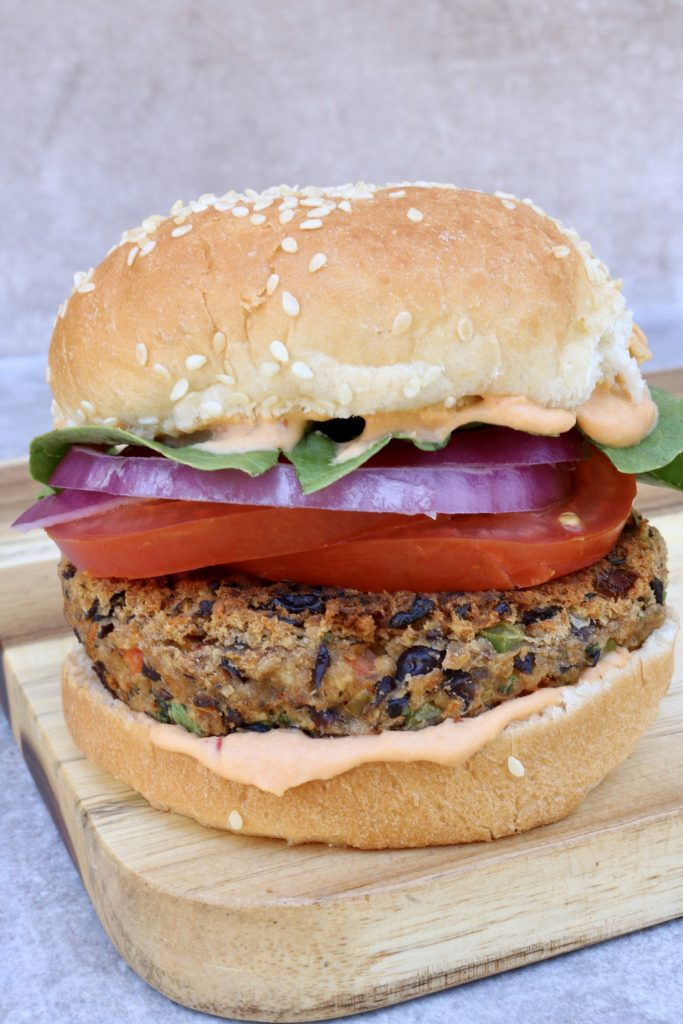 Close up, Black Bean Burger with Chipotle Hummus on a bun with lettuce tomato and red onion.