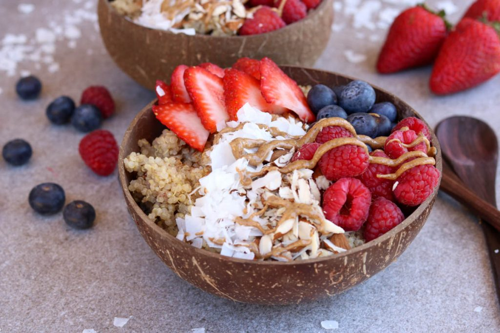 Breakfast quinoa bowl topped with berries, coconut and almond butter with another bowl in the background.