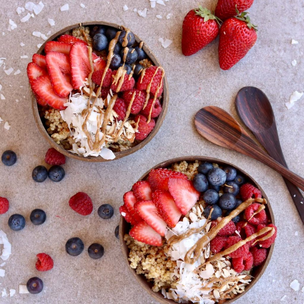 Overhead, two bowls filled with breakfast quinoa topped with berries and almond butter.
