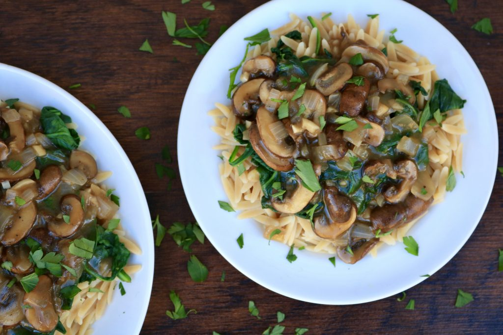 Two white plates served with Mushroom Marsala Sauce with Orzo and Spinach and sprinkled with parsley.