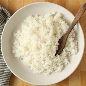 Overhead, rice on a plate with a wooden fork and stripped tea towel.