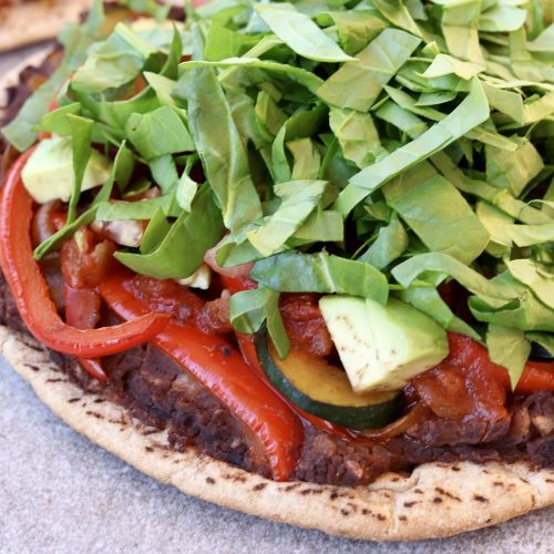 Mexican Pita Pizza topped with refried black beans, sautéed vegetables, avocado and spinach.