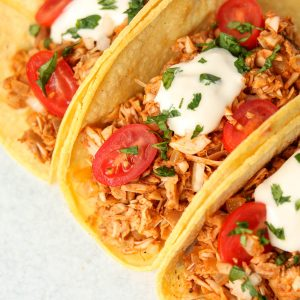 Finished tacos with sour cream, tomatoes and cilantro on top.