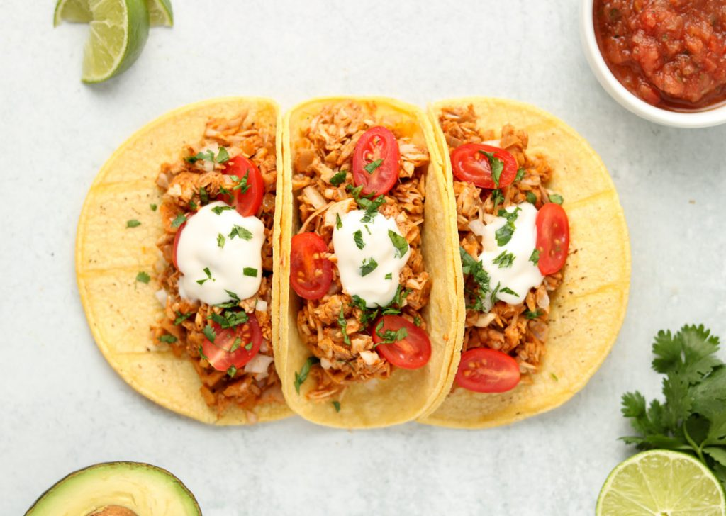 Over head, finished tacos garnished with sour cream, cilantro and tomatoes.