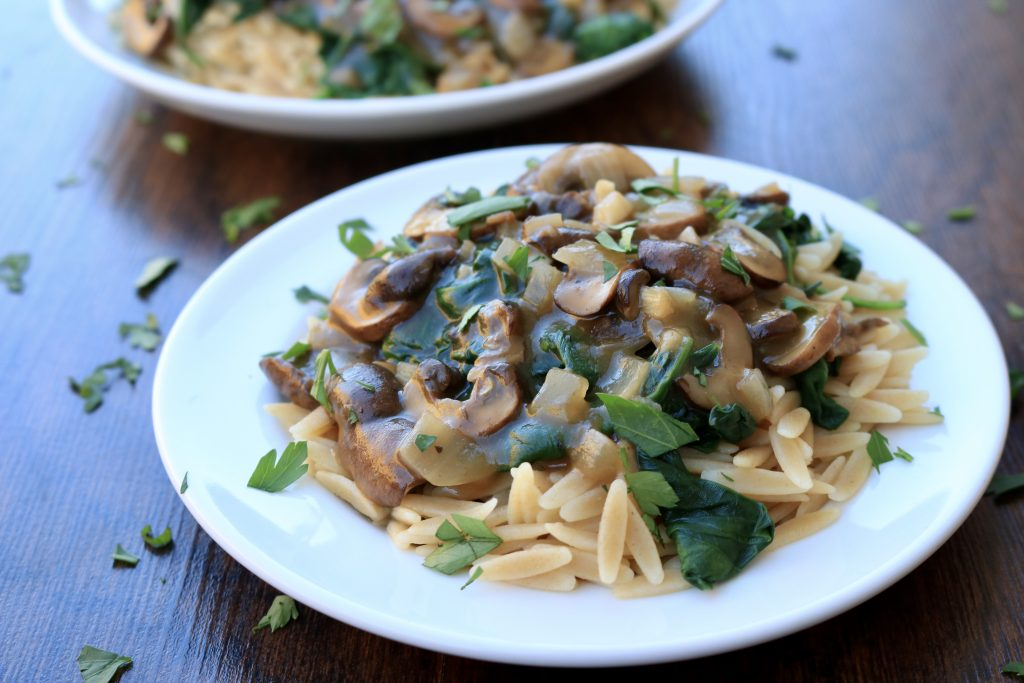Two white plates served with Mushroom Marsala with Orzo and Spinach and sprinkled with parsley.