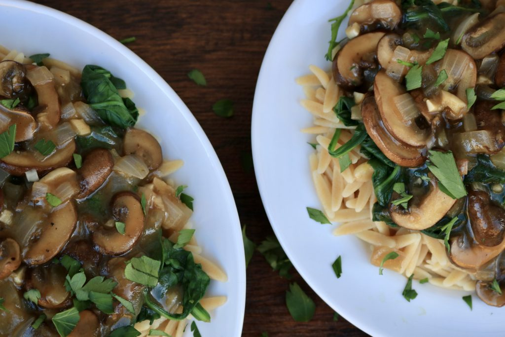 Close up, Two white plates served with Mushroom Marsala with Orzo and Spinach and sprinkled with parsley.