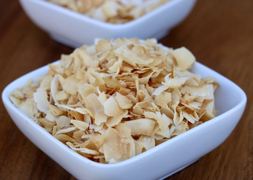 Close up, toasted coconut flakes in a ramikin.