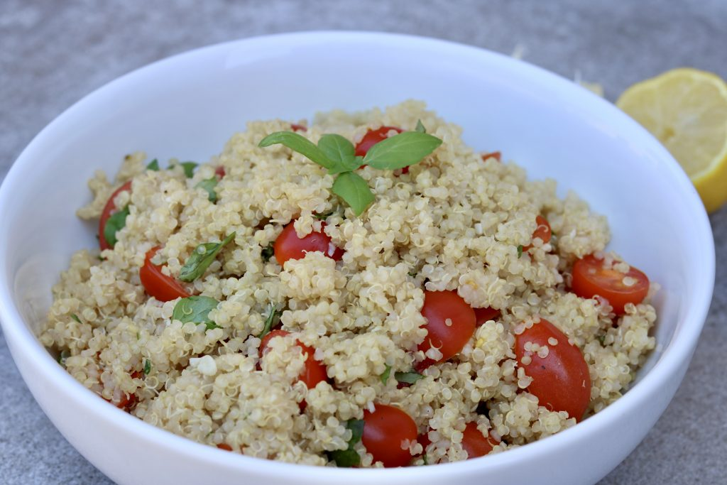 Big bowl full of Easy Tomato Basil Quinoa with basil on top and basil, garlic and lemon in the background.