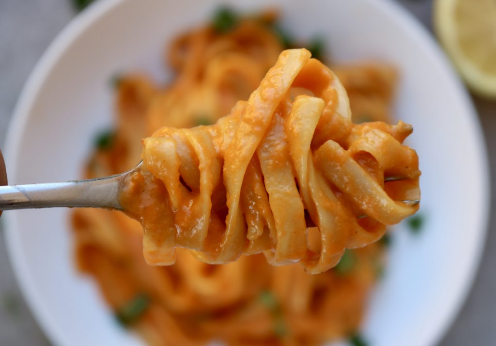 Vegan Roasted Red Pepper Pasta on a fork with a plate of pasta in the background.