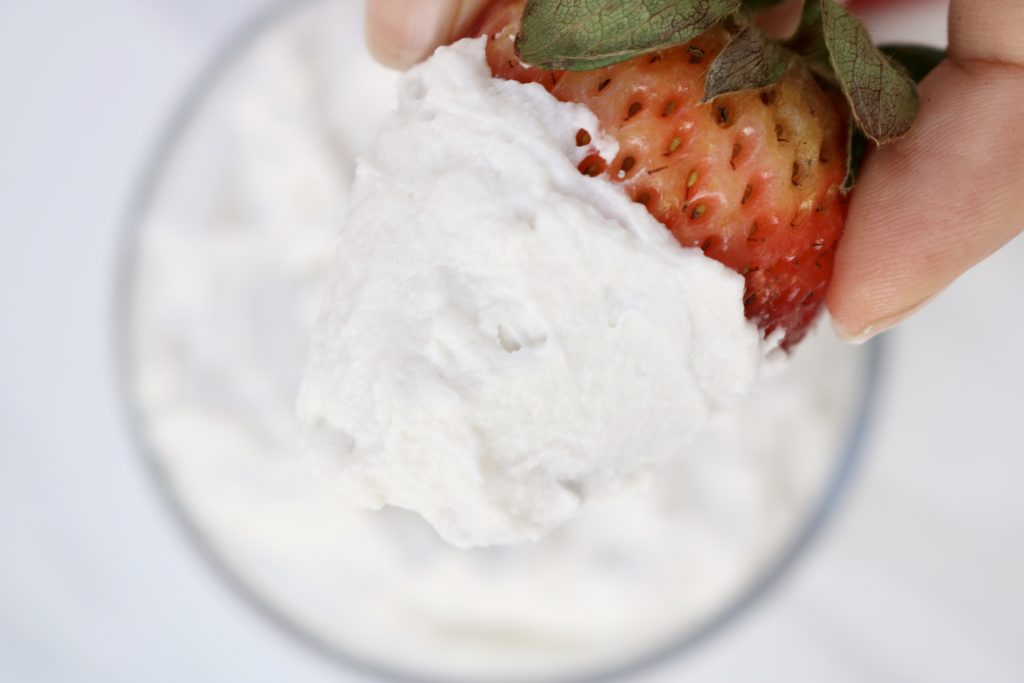 Close up, strawberries dipped in Vegan Coconut Whipped Cream with a bowl of the whipped cream in the background.