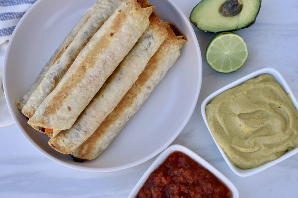 Sweet Potato & Black Bean Baked Taquitos on a plate, served with Avocado Cream and salsa.