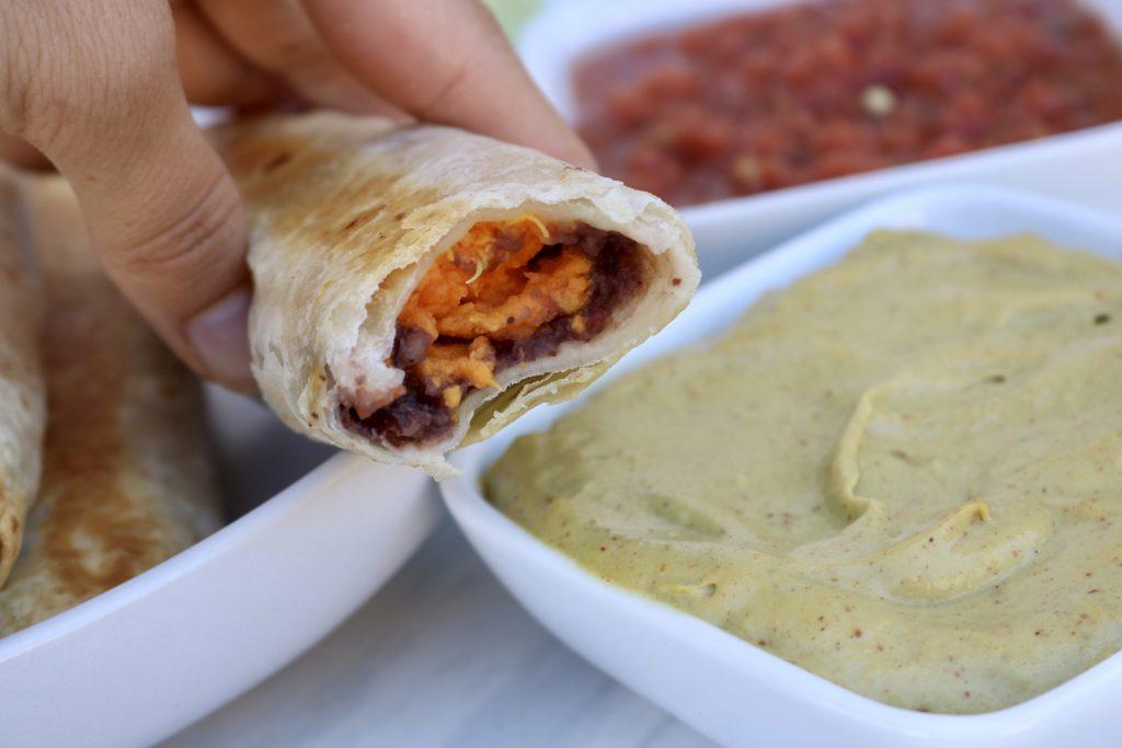 Close up Sweet Potato & Black Bean Baked Taquitos with avocado cream and salsa.