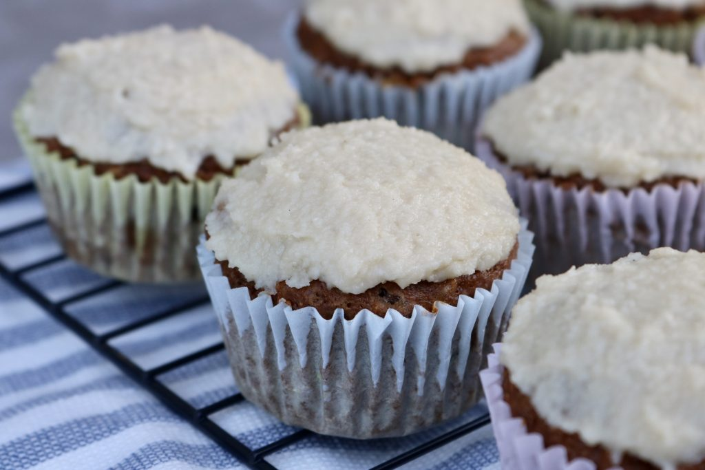 Carrot Cake Cupcakes with Coconut Macadamia Nut Frosting on a wire rack.