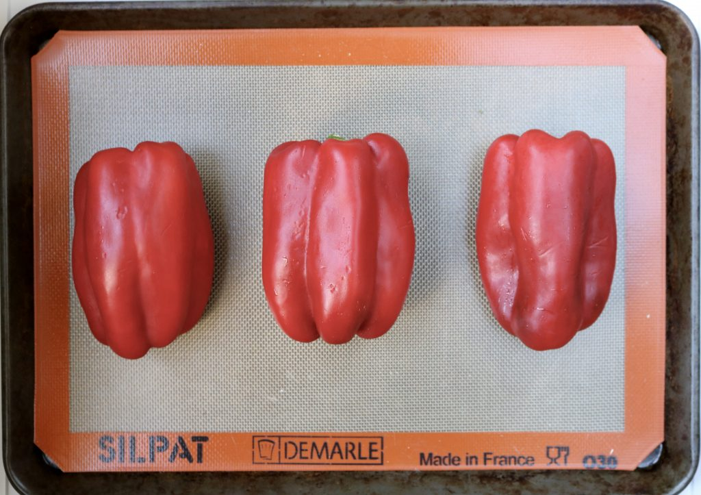 Three Red Bell Peppers on a sheet pan with a Silpat mat.
