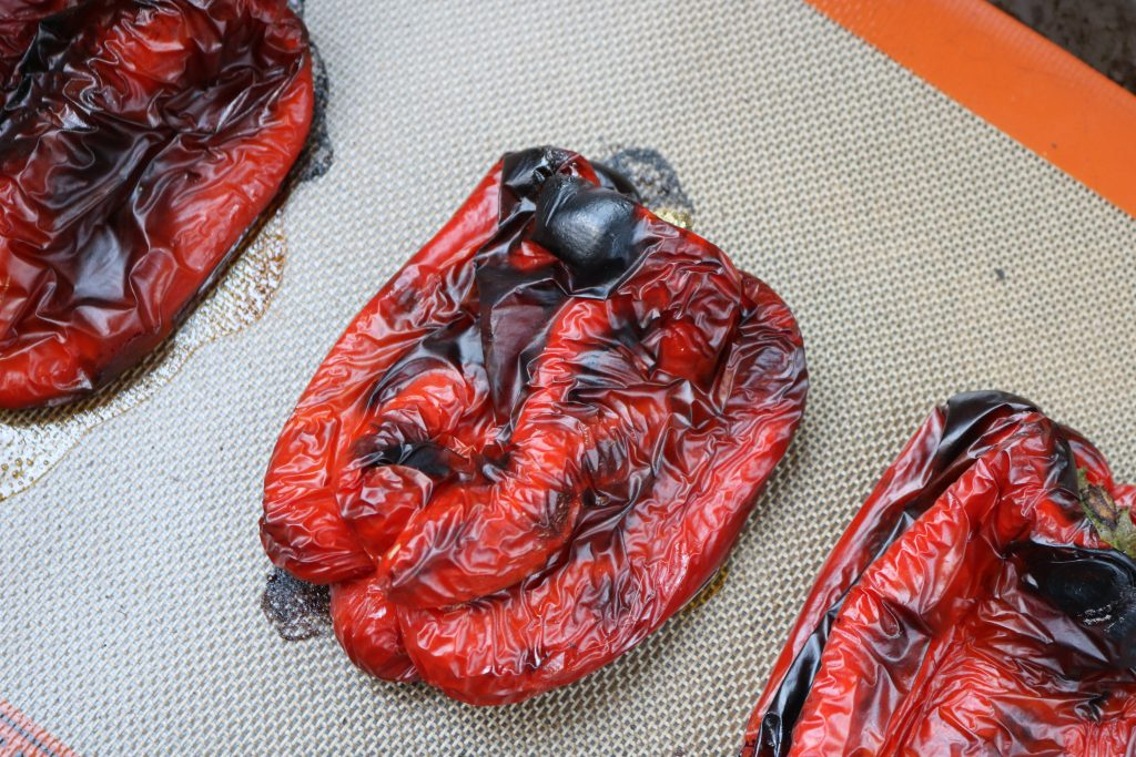 Close up, Three Roasted Red Bell Peppers on a sheet pan with a Silpat mat.