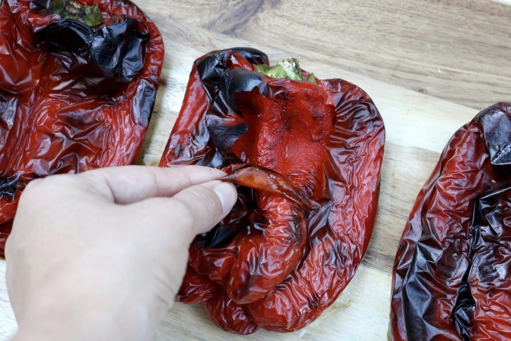Close up, Roasted Red Bell Pepper with the skin being peeled off.