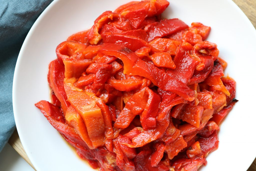 Roasted Red Bell Peppers cut into stips in a white bowl with a blue kitchen towel next to the bowl.