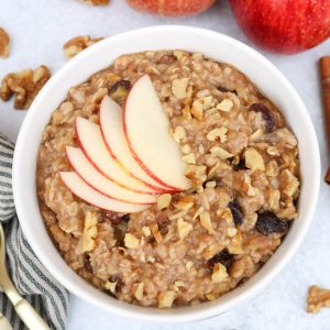 Bowl of apple cinnamon oatmeal topped with fanned apples with scattered walnuts, apples and cinnamon sticks in the background.