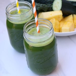 Two mason jars filled with Blender Green Juice Recipe with fruit and vegetables in the background.