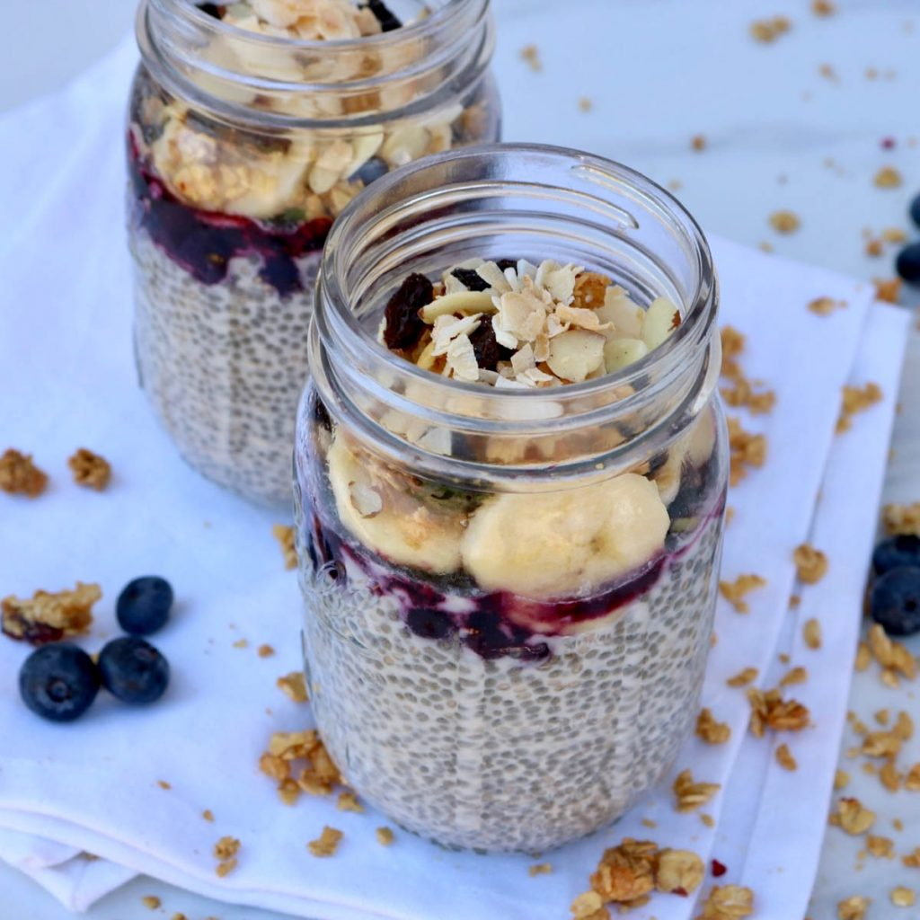Two mason jars filled with Overnight Vegan Chia Seed Pudding topped with blueberry compote, sliced banana, granola and toasted coconut.