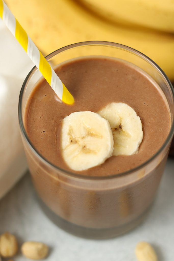 Closeup, smoothie finished in a glass with sliced bananas on top and a yellow stripped straw.