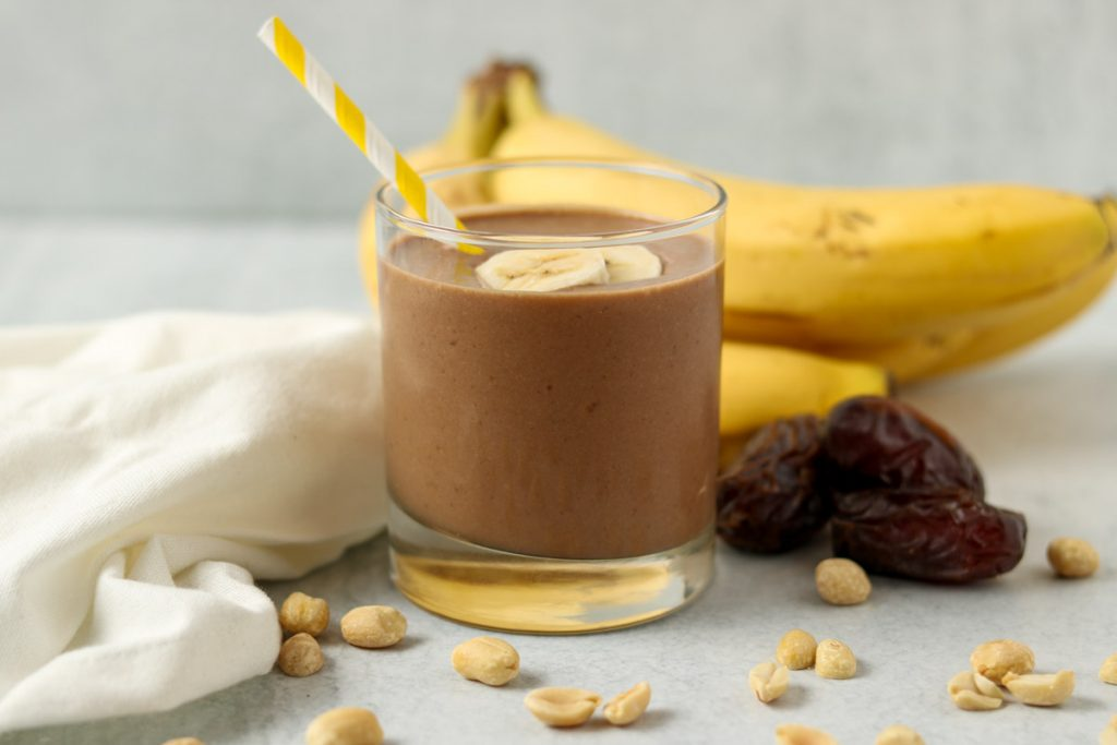 Finished chocolate peanut butter banana smoothie in a glass with a towel, dates, bananas and peanuts in the background.