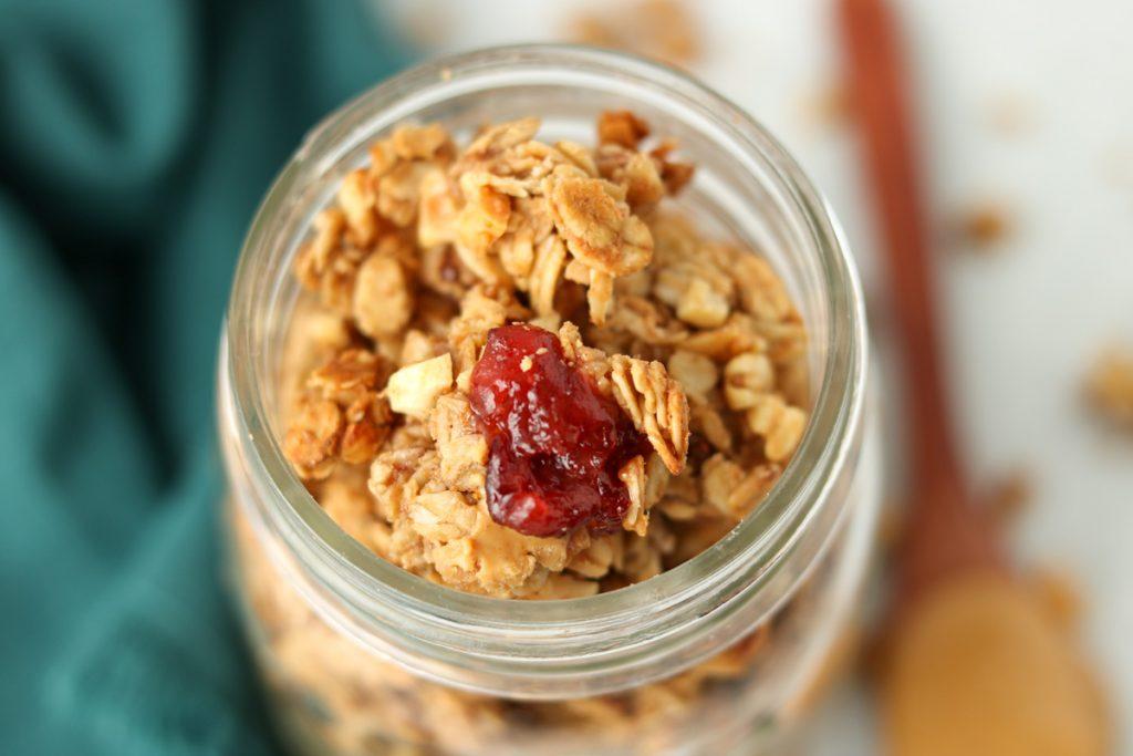 Close up finished granola in mason jar.