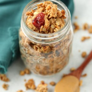 Finished granola in mason jar with spoon of peanut butter and granola scattered around.