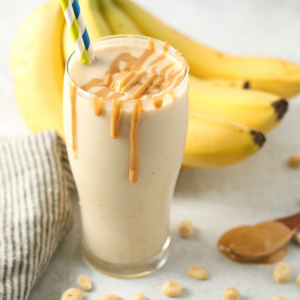 Finished smoothie in a glass with two straws drizzled with peanut butter with bananas, peanuts and a stripped towel in the background.