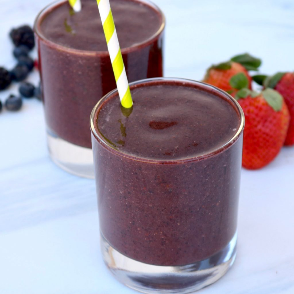 Close up, spinach berry smoothie with fruit in the background and a stripped straw.