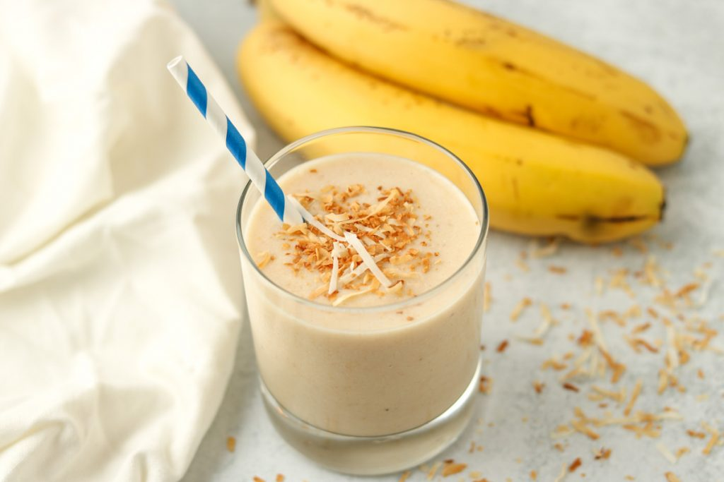Finished smoothie with toasted coconut on top and a straw.