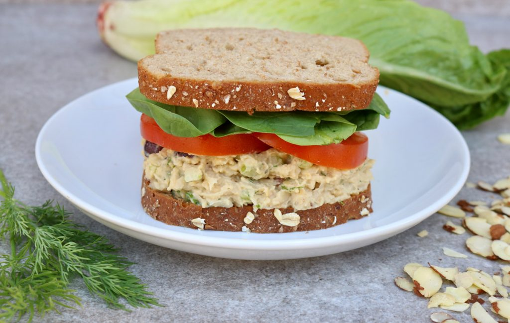 Vegan chicken salad sandwich with tomatoes and lettuce on a white plate.