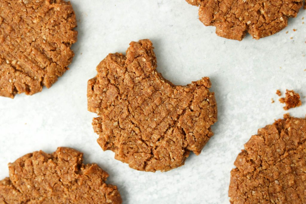 Close up, single cookies with a bite out of it with other cookies around.