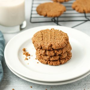 Three cookies stacked on one another with more cookies on a baking rack in the background, a glass of almond milk and a blue tea towel.