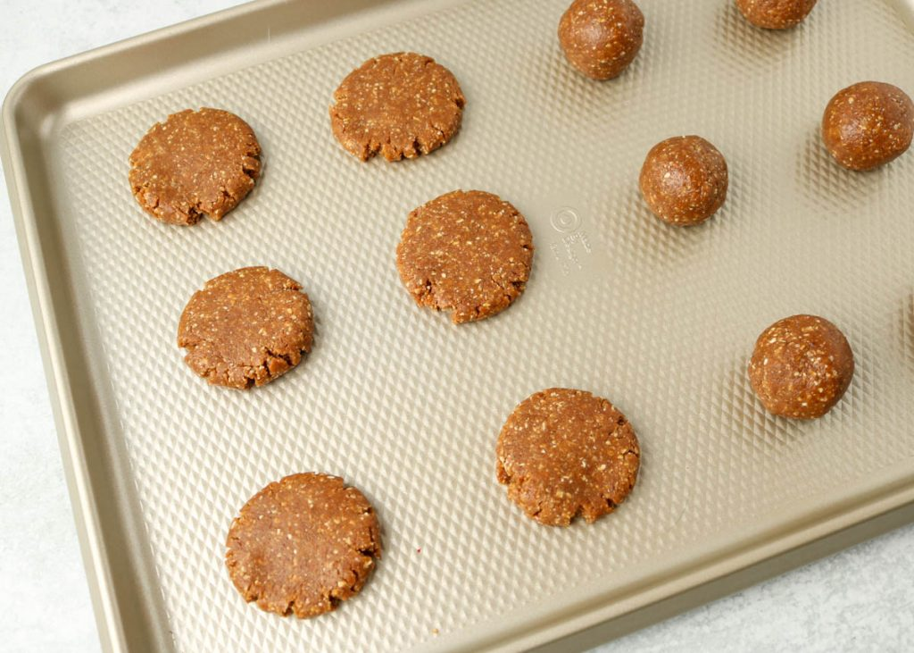 Cookies on a sheet pan pressed down with hand.