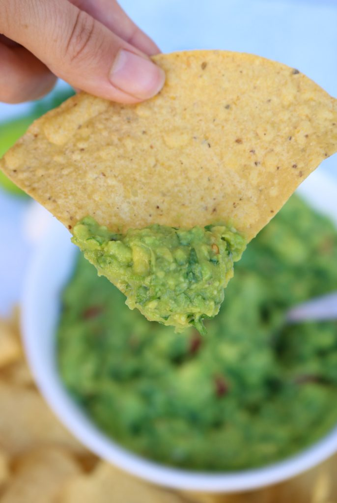 Close up of a tortilla chip with guacamole on it, with white bowl of guacamole in the background.