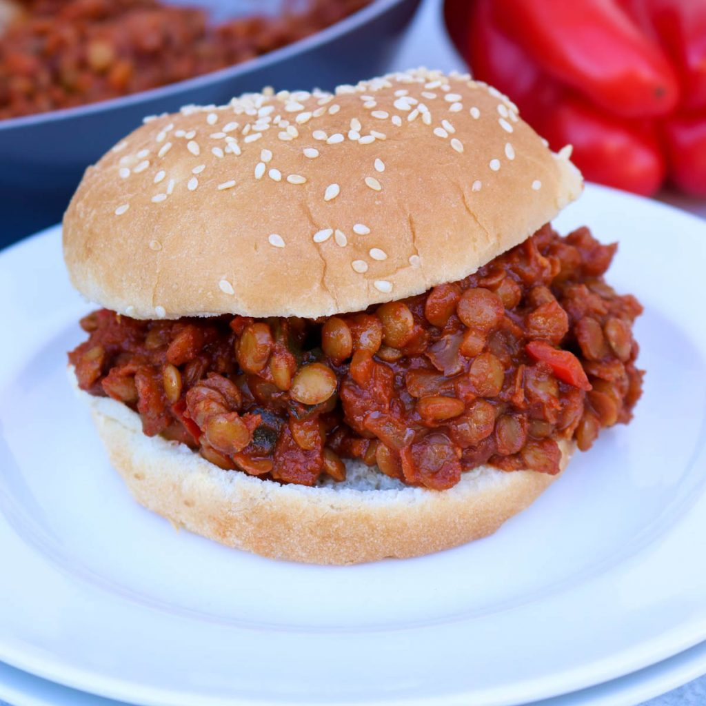 Close up, White plate with sloppy joe an pan of lentil mix in the background with red bell pepper int he background as well.