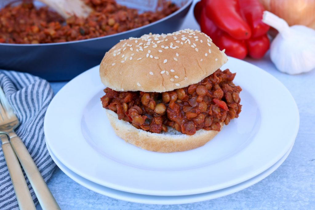 Stacked white plates with finished vegan lentil sloppy joe with a pan of the mix and vegetables in the background as well as a stripped napkin and gold fork.