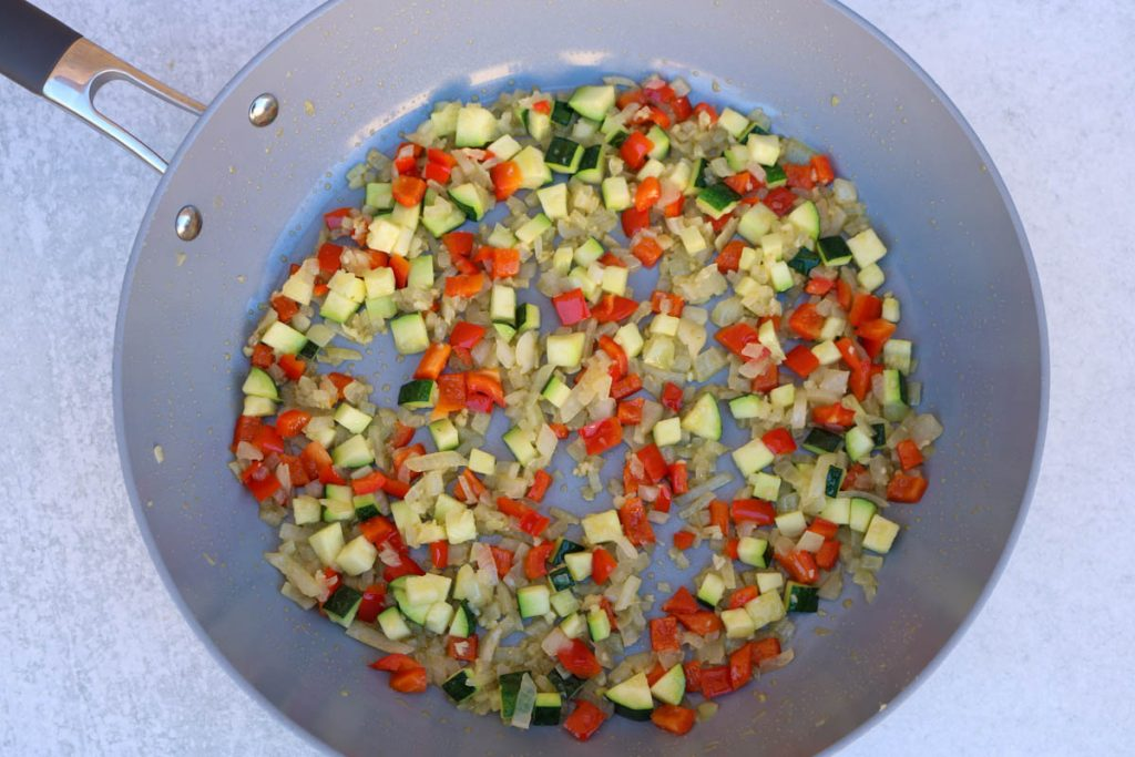 Garlic, onion and vegetables sautéed in a pan.