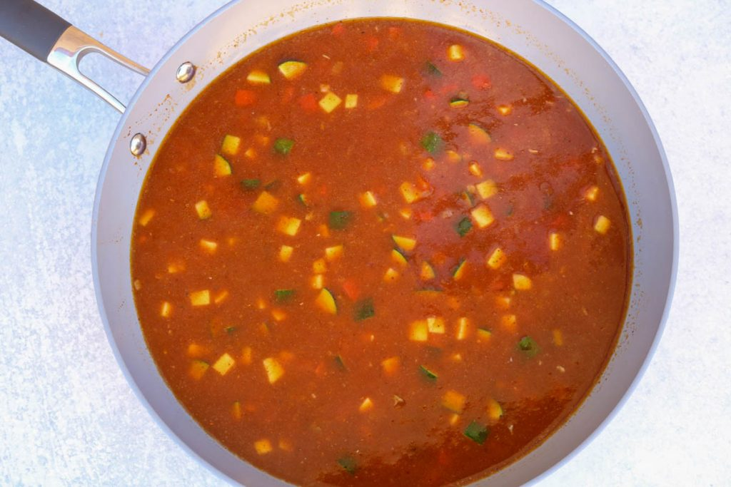 Tomato sauce added to vegetable mix and stirred in a pan.