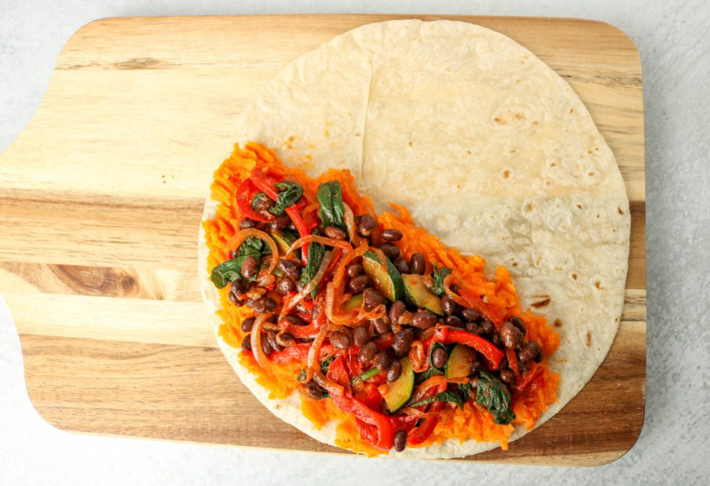 Open tortilla on a cutting board filled with ingredients.