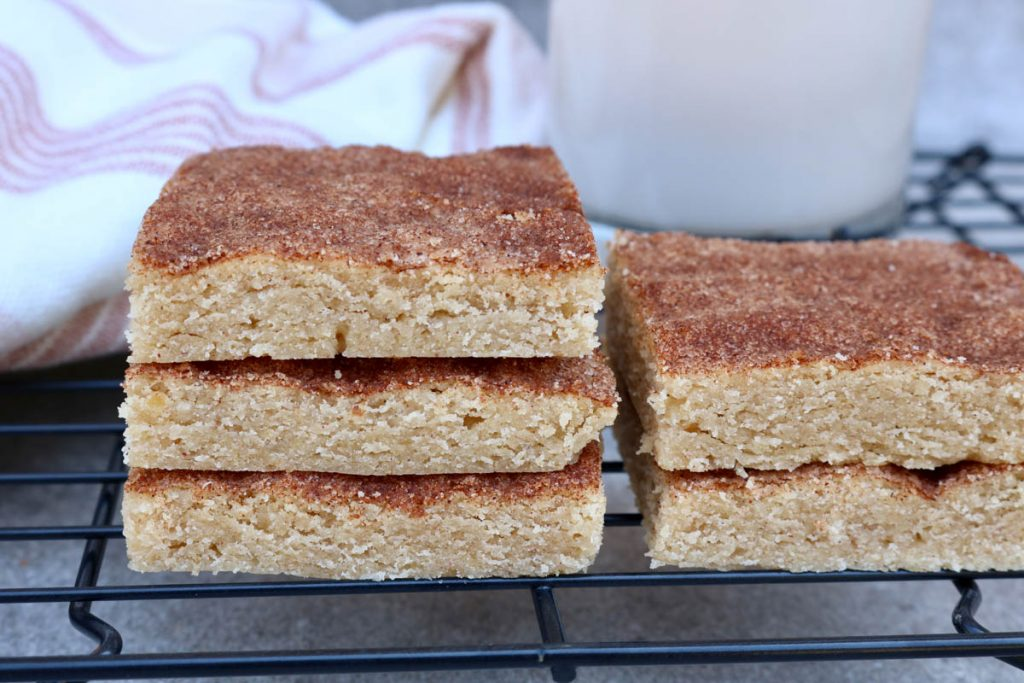 Three snickerdoodle bars stacked on top of one another with more bars next to them a stripped towel and glass of milk in the background.
